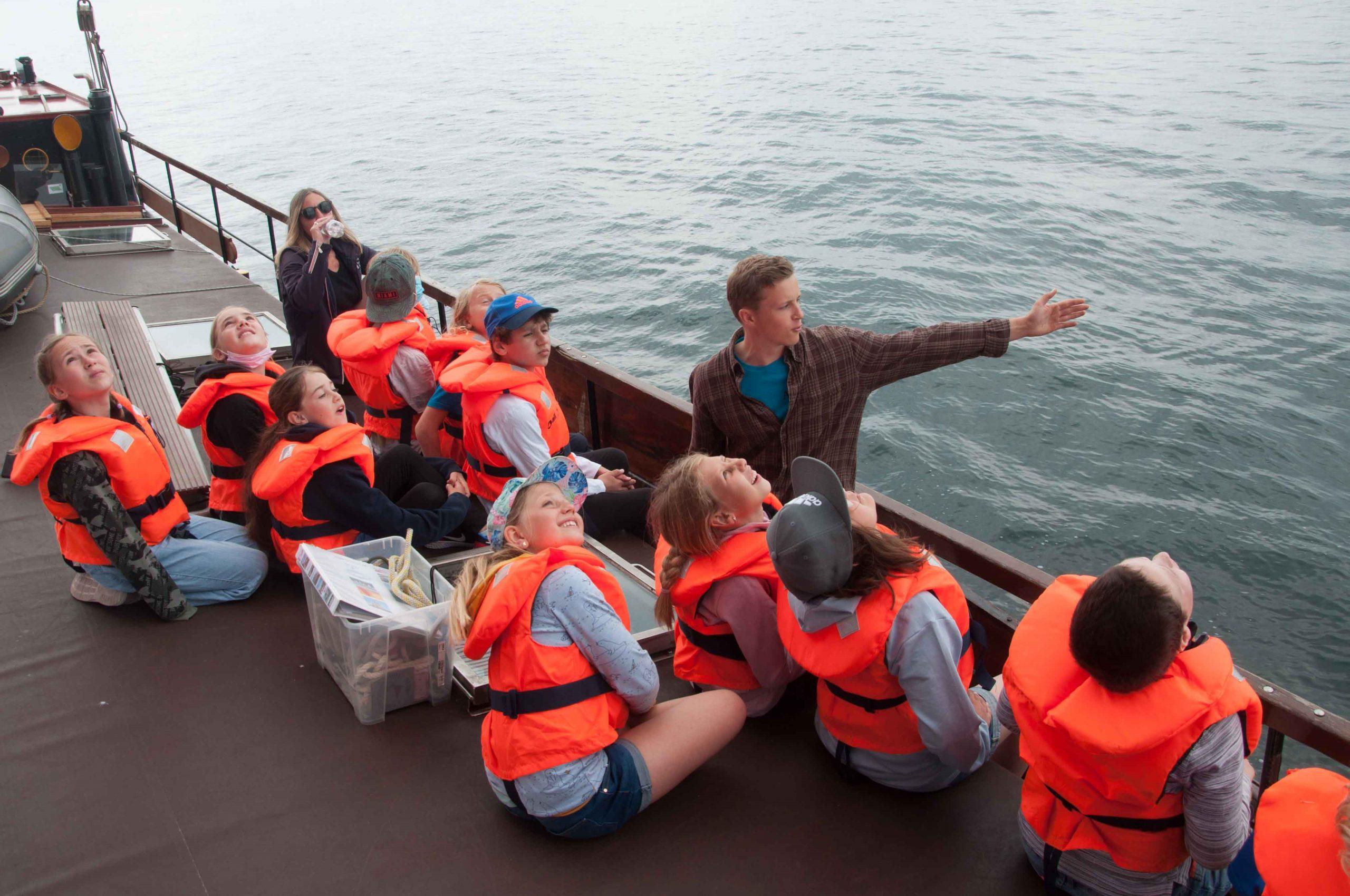 Wo Marc hier hinzeigt, bleibt dem Betrachter ein Rätsel. Sein gestreckter Arm zeigt wahrscheinlich zum Kieler Leuchtturm, aber seine jungen Zuhörer schauen alle nach oben.