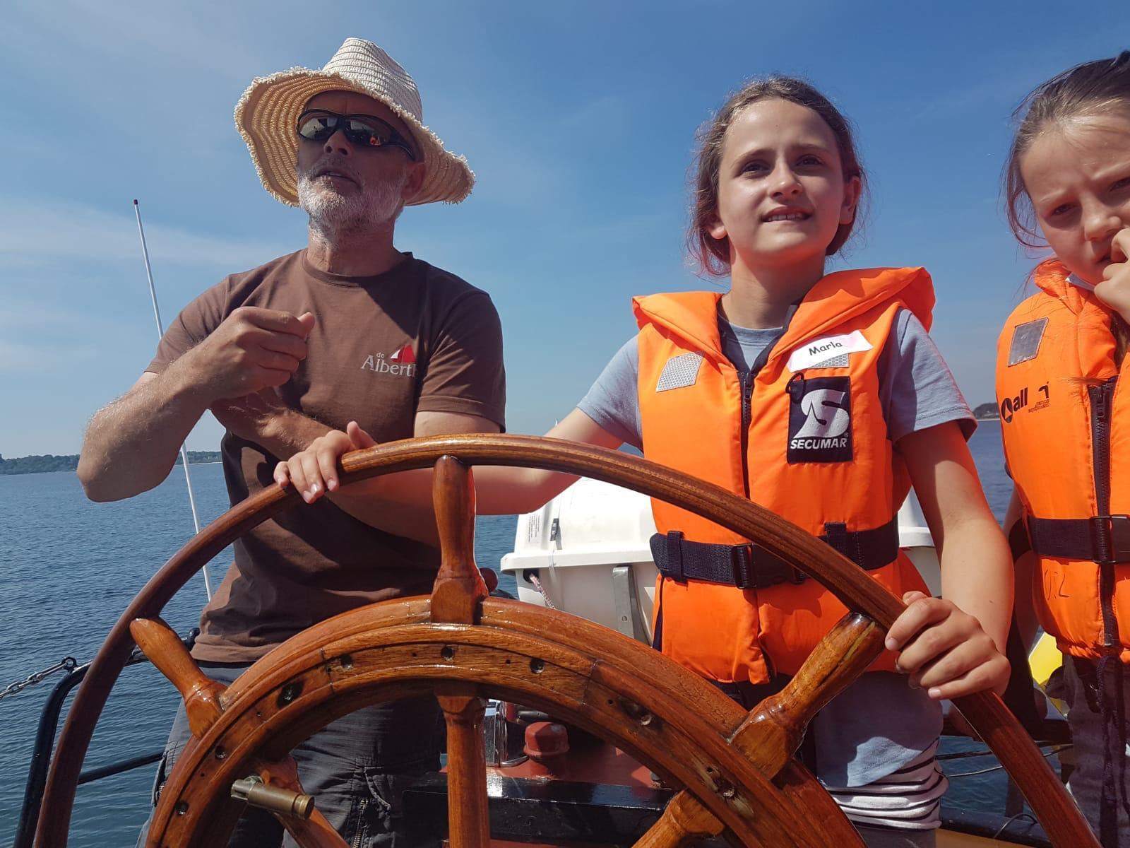Auch Marla mit ihrer Assistentin lässt sich vom Skipper Dick zeigen, wie man die gute, alte Dame DE ALBERTHA sicher auf Kurs hält.